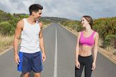Portrait of a fit young couple standing on the open road