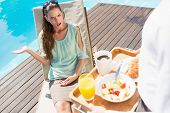 Upset young woman looking at cropped waiter with breakfast tray by the pool