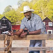 A mature African American cowboy happily looking at the viewer while leaning against a rustic rail f