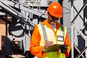 happy african electrician writing on clipboard in electric substation