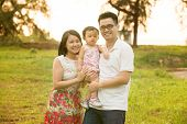 Happy Asian family portrait. Outdoor playing time during summer sunset.
