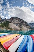 image of tens  - A fisheye view of Moraine Lake in the Canadian Rockies with vibrant colored canoes on the foreground and the Valley of the Ten Peaks in the background - JPG
