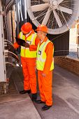 two technicians discussing wiring in substation