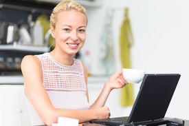 stock photo of independent woman  - Happy business woman working from her home having more time for her family and her morning coffee - JPG