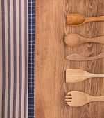 Blue and off white kitchen towels on dark wood background with wooden kitchen utensils, and copy space in the center