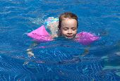 Joyful little girl swimming in the pool.