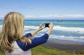 Woman taking a photo at the beach with her smartphone
