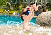 Active Father Teaching His Toddler Daughter To Swim In Pool On Tropical Resort . Summer Vacations An