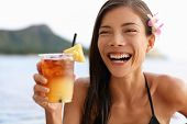 Hawaii woman drinking Mai Tai hawaiian drink. Asian tourist on holiday partying on Honolulu Waikiki beach, Oahu.