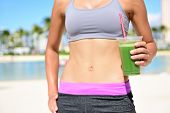 Fitness woman drinking green vegetable smoothie after running exercise.  Close up of smoothie and stomach. Healthy lifestyle concept with fit female model outside on beach.