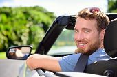 Car driver - young man wearing safety belt driving convertible on road trip in summer. Caucasian male looking at camera.