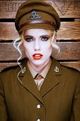 Attractive blond fashion model wearing makeup with her hair curled in ringlets in a brown army uniform and peaked cap, head and shoulders portrait