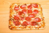 Square Pepperoni Sausage And Ham Pizza On Wood Table
