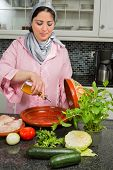 Traditional Moroccan immigrant woman in Europe adding olive oil to her tajine during Ramadan in her modern kitchen