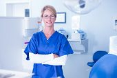 pic of dentist  - Portrait of a dentist smiling at camera with arms crossed at the dental clinic - JPG
