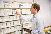 Handsome pharmacist taking medicine from shelf at the hospital pharmacy