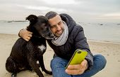 foto of nonverbal  - Man helping his dog making selfie image using a smartphone - JPG
