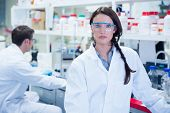 Unsmiling chemist standing in front of her colleague in the laboratory