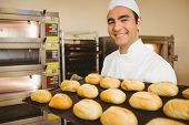 Baker smiling at camera holding tray of rolls in a commercial kitchen