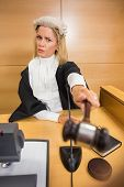 picture of court room  - Stern judge pointing her hammer in the court room - JPG