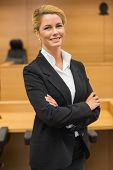 stock photo of court room  - Smiling lawyer looking at camera in the court room - JPG