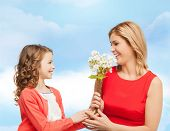 people, holidays, relations and family concept - happy little daughter giving flowers to her mother over blue sky background