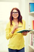 education concept - smiling redhead female student in eyeglasses with book and pencil in library