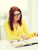 education concept - smiling student girl in eyeglasses reading books in college