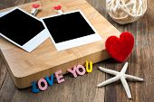 Two Blank Instant Photos With Red Hearts.on Wooden Background