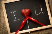 Red Heart Lying On Blackboard With Written Declaration Of Love