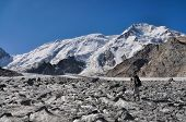 picture of shan  - Young adventurer with backpack on glacier below snow-covered highest peaks in Tien-Shan mountain range in Kyrgyzstan ** Note: Soft Focus at 100%, best at smaller sizes - JPG