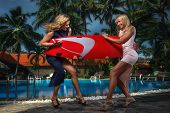 Pretty girls with surfboard on a resort