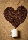 stock photo of mug shot  - Closeup macro shot of heart of coffee beans going from white mug lying on canvas - JPG