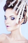 Close up of beautiful model with winter makeup over blue background. Snow queen.