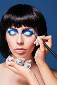 Eye makeup woman applying blue eyeshadow powder
