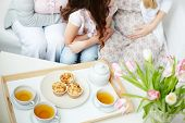 pic of grandmother  - Cups of green tea and muffins on tray with little girl - JPG