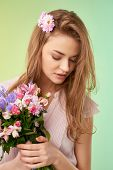 Gorgeous girl holding bunch of various flowers