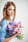 Pretty young lady with flowers looking at camera