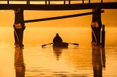 Beautiful sunset by the river. Fisherman is in the boat
