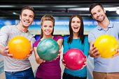 foto of cheers  - Cheerful friends looking at camera and outstretching their balls while standing against bowling alleys - JPG