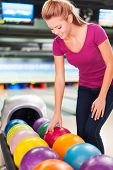 picture of bowling ball  - Cheerful young women choosing bowling ball and smiling while standing against bowling alleys - JPG