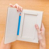 Woman hand holding notebook on wooden background
