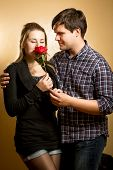 Young Woman Smelling Red Rose Presented By Young Man