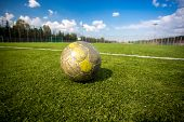 Shabby Soccer Ball Lying On Artificial Grass Field