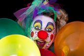 foto of clown face  - A colored clown face looks between colorful balloons in to the camera