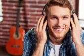 foto of nod  - Handsome young man adjusting his headphones and smiling while acoustic guitar laying in the background - JPG