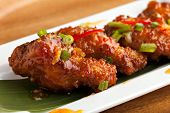 stock photo of fried chicken  - Thai style spicy chicken wings appetizer on a contemporary white plate - JPG