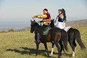 People in national dresses ride on horseback, Almaty, Kazakhstan.