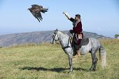 Mongolian man launches golden eagle to hunt circa Almaty, Kazakhstan.