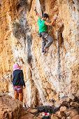 Man lead climbing on cliff, belayer watching hi